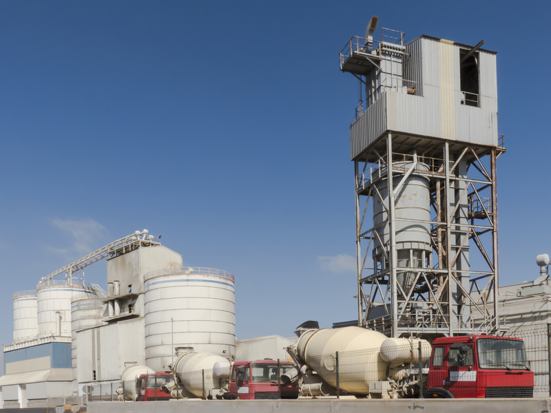 Cement factory with trucks in line waiting to load betontherm, construction material for delivery.